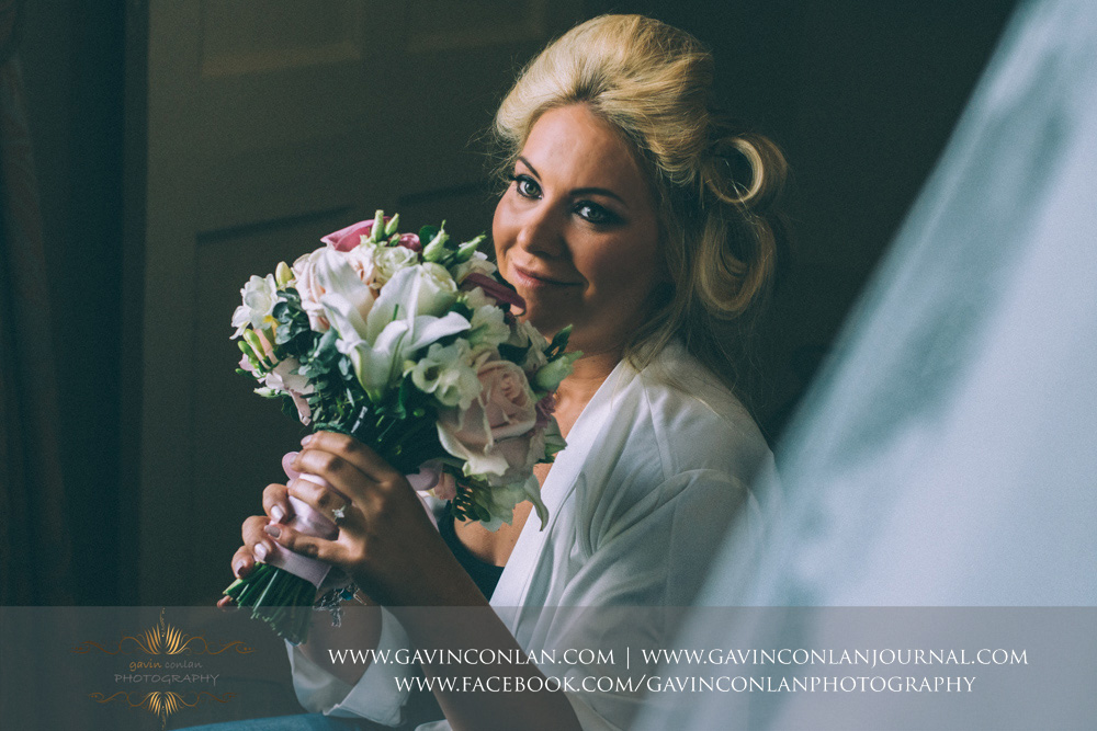 the bride holding her flowers whilst she is having her make up done.Wedding photography at  The SPA Hotel  by  gavin conlan photography Ltd