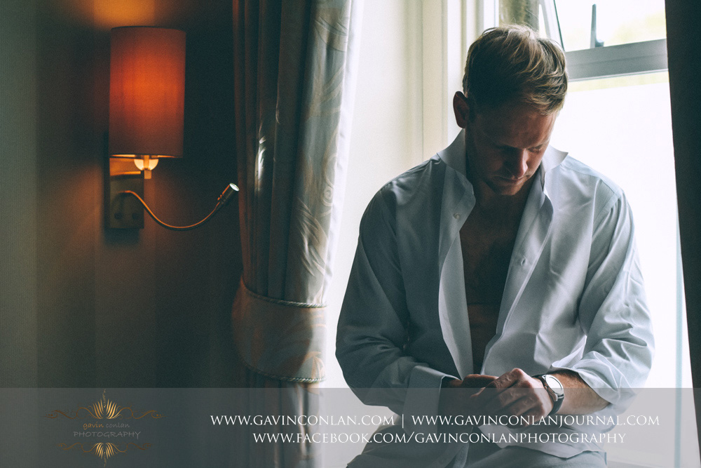 creative portrait of the groom getting dressed. Wedding photography at  The SPA Hotel  by  gavin conlan photography Ltd