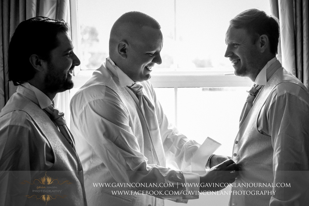 creative black and white portrait of the best man and usher helping the groom get dressed.Wedding photography at  The SPA Hotel  by  gavin conlan photography Ltd
