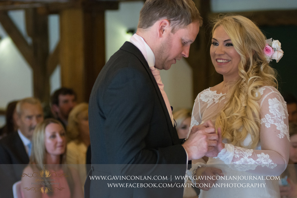 the groom placing thewedding ring on his brides finger whilst she is looking so happy.Wedding photography at  High Rocks  by preferred supplier gavin conlan photography Ltd