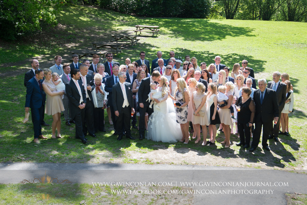 the group photograph of all theguests with the bride and groom in the grounds of The Rocks during their drinks reception.Wedding photography at  High Rocks  by preferred supplier gavin conlan photography Ltd