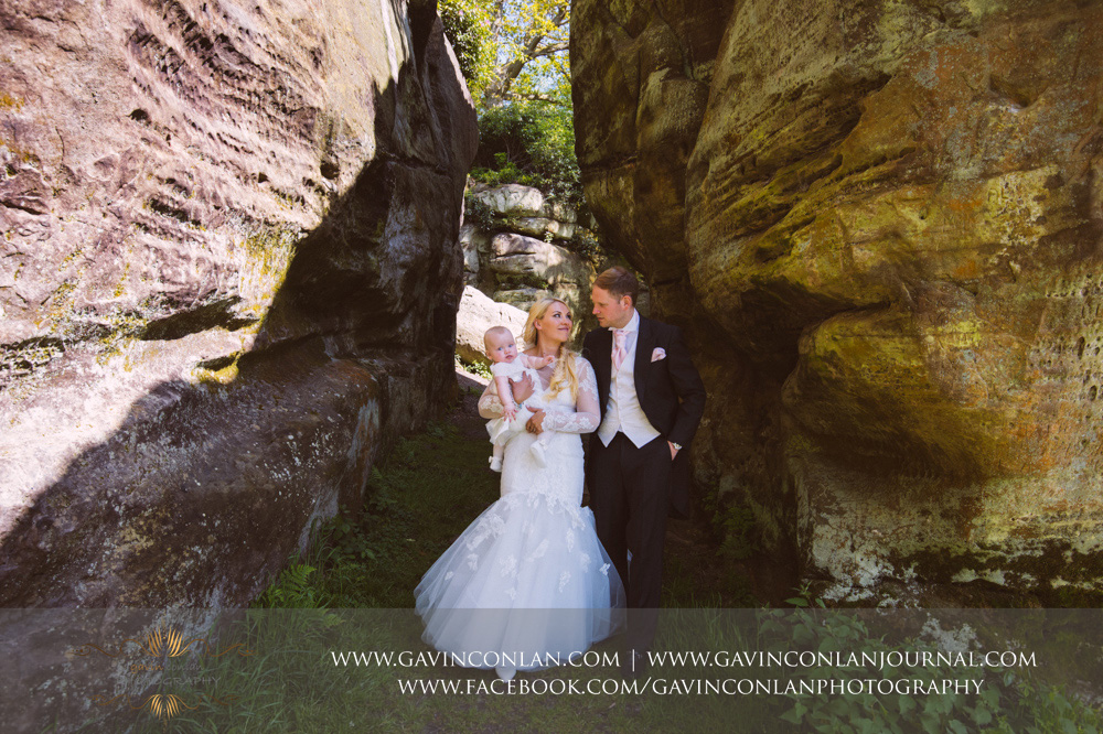 creative portrait of the bride and groom with their beautiful daughter in the grounds of The Rocks.Wedding photography at  High Rocks  by preferred supplier gavin conlan photography Ltd