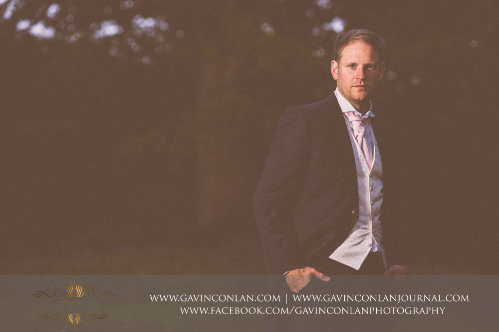 creative portrait of the groom taken at the top of The Rocks at dusk.Wedding photography at  High Rocks  by preferred supplier gavin conlan photography Ltd