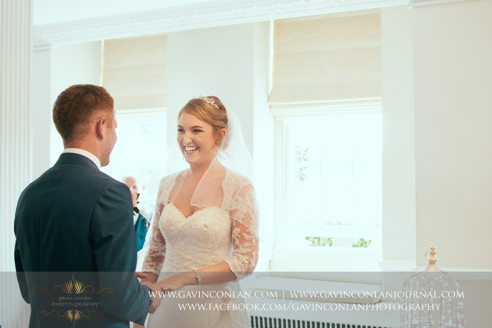 creative portrait of the bride looking at her groom smiling - a beautiful moment during their wedding ceremony. Wedding photography at  Parklands Quendon Hall  by preferred supplier  gavin conlan photography Ltd