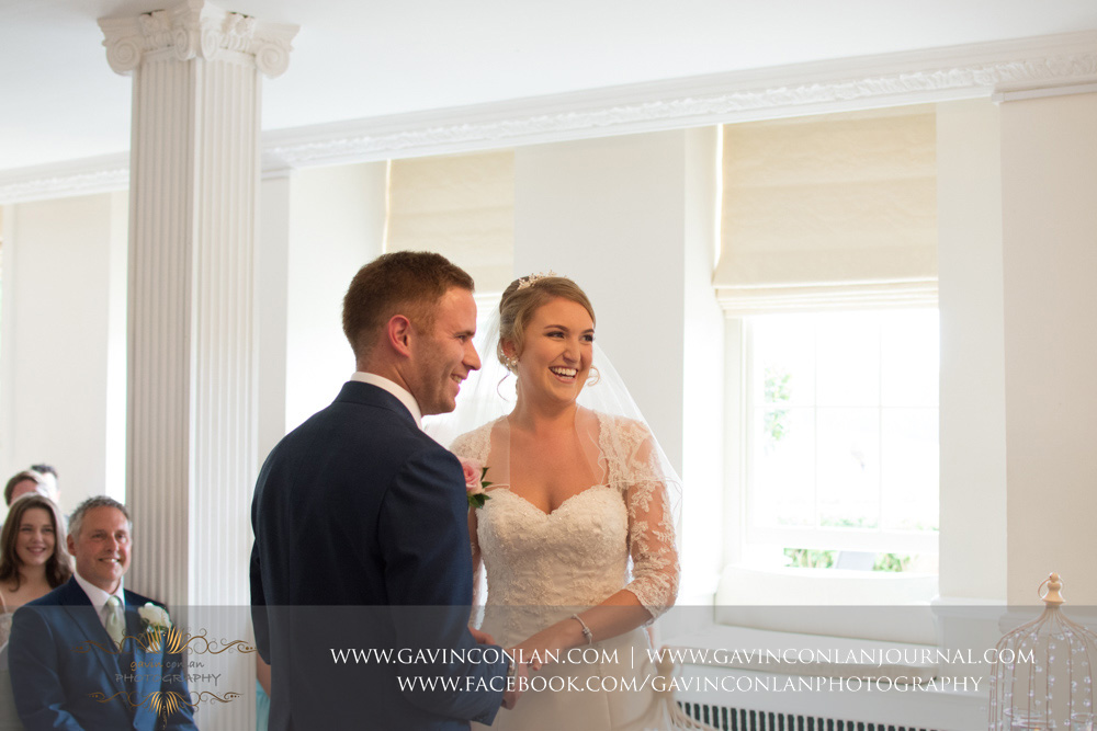 creative portrait of the bride and groom both smiling and laughing - a beautiful moment during their wedding ceremony. Wedding photography at  Parklands Quendon Hall  by preferred supplier  gavin conlan photography Ltd
