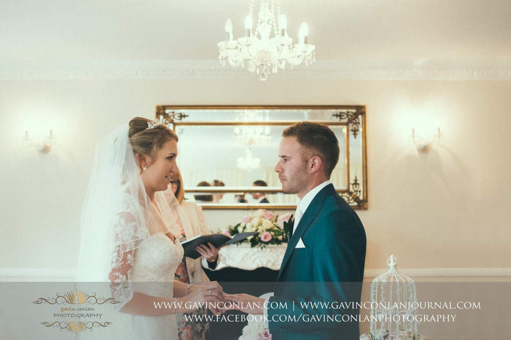creative portrait of the bride putting the wedding ring on her grooms finger during the wedding ceremony. Wedding photography at  Parklands Quendon Hall  by preferred supplier  gavin conlan photography Ltd