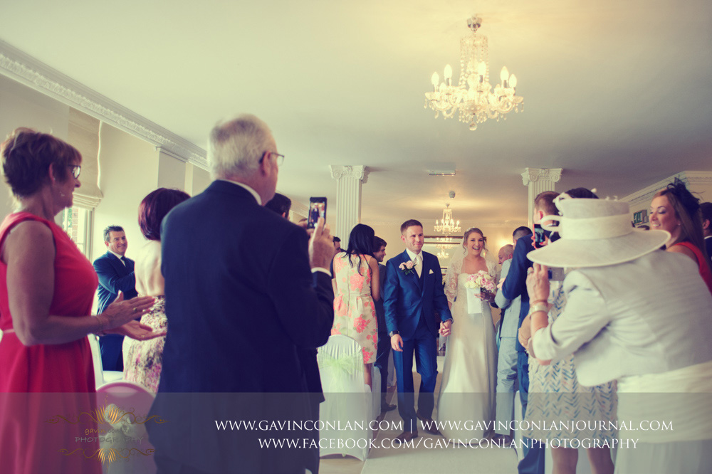 Mr and Mrs Sturgeon walk down the aisle as a married couple to close their wedding ceremony. Wedding photography at  Parklands Quendon Hall  by preferred supplier  gavin conlan photography Ltd