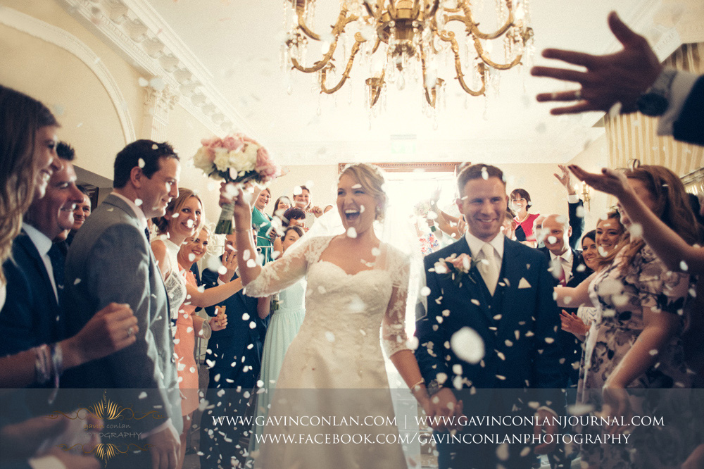 creative portrait of the guests throwing confetti over the bride and groom - beautiful expressions of happiness. Wedding photography at  Parklands Quendon Hall  by preferred supplier  gavin conlan photography Ltd