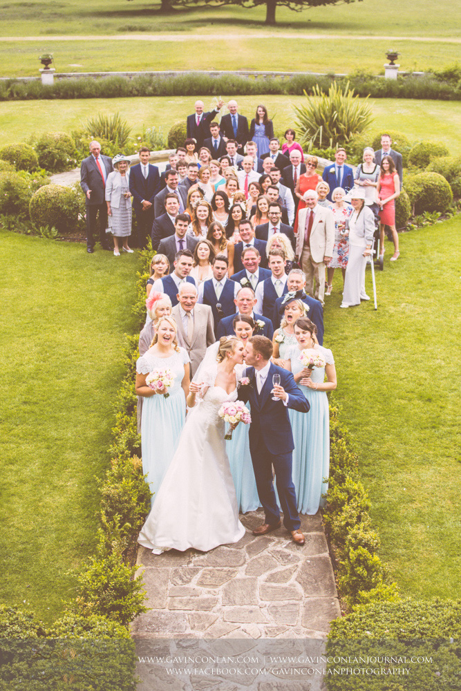 creative portrait of all the guests with the bride and groom kissing at the front of the group photograph. Wedding photography at  Parklands Quendon Hall  by preferred supplier  gavin conlan photography Ltd