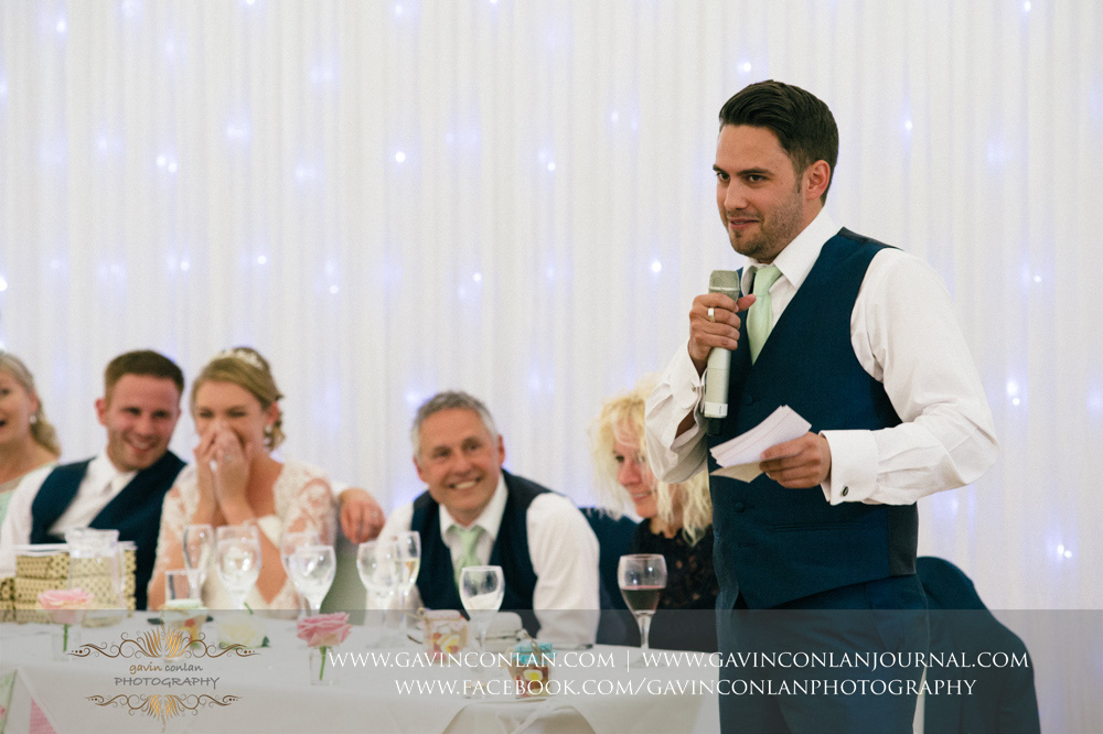 creative portrait of one of the best men during his speech with the top table all laughing in the background. Wedding photography at  Parklands Quendon Hall  by preferred supplier  gavin conlan photography Ltd