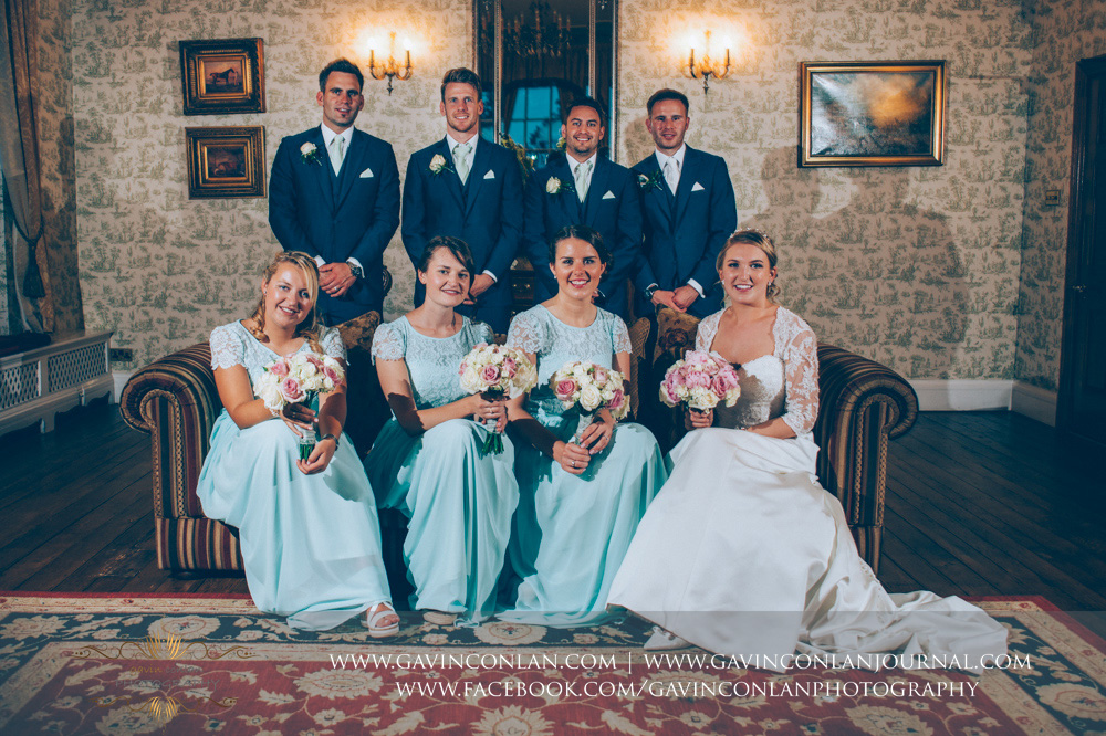 creative portrait of the bride, groom, bridesmaids and best men in the drawing room. Wedding photography at  Parklands Quendon Hall  by preferred supplier  gavin conlan photography Ltd
