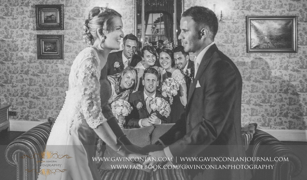 creative and fun black and white portrait of the bride and groom holding hands with the bridesmaids and best men looking on in the drawing room. Wedding photography at  Parklands Quendon Hall  by preferred supplier  gavin conlan photography Ltd
