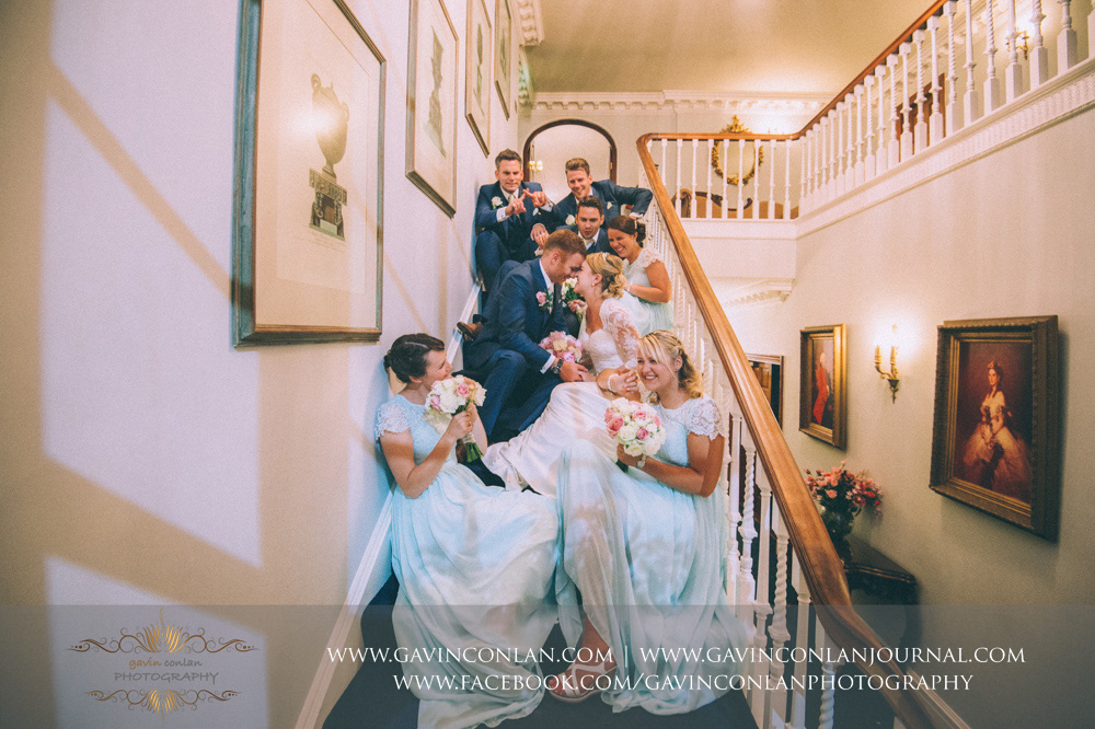 creative and fun portrait of the bride, groom, bridesmaids and best men posing on the staircase inside Parklands. Wedding photography at  Parklands Quendon Hall  by preferred supplier  gavin conlan photography Ltd
