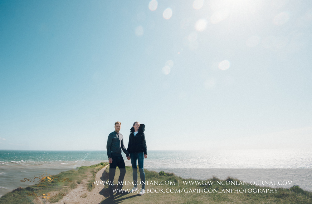 creative portrait of the couple holding hands on the edge of the chalk ridge at  Old Harry Rocks . Victoria and James Engagement Session in Bournemouth, Dorset by  gavin conlan photography Ltd
