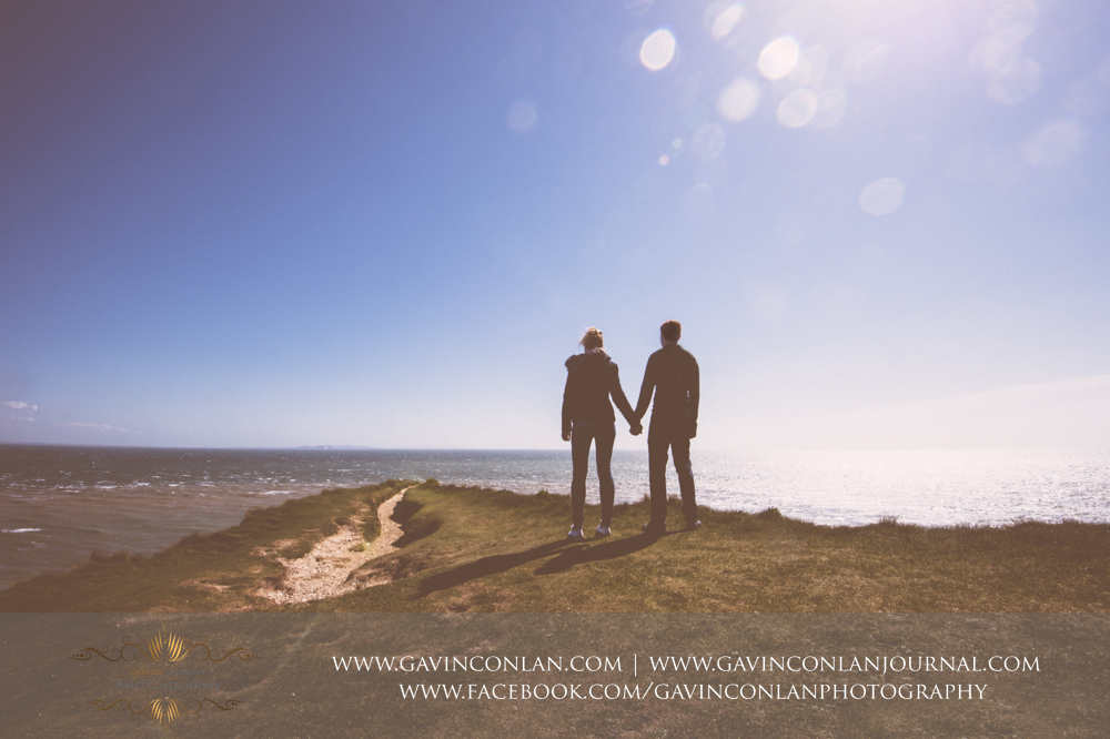creative portrait of the couple holding hands looking out over the Solent on the edge of the chalk ridge at  Old Harry Rocks . Victoria and James Engagement Session in Bournemouth, Dorset by  gavin conlan photography Ltd