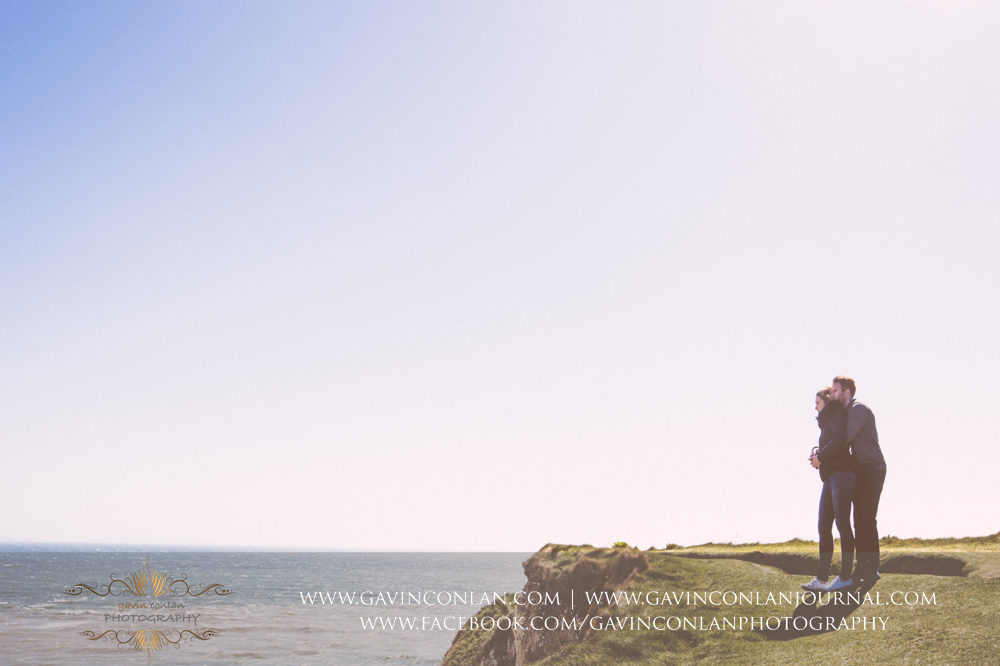 creative portrait of the couple cuddling whilst looking out over the Solent on the edge of the chalk ridge at  Old Harry Rocks . Victoria and James Engagement Session in Bournemouth, Dorset by  gavin conlan photography Ltd