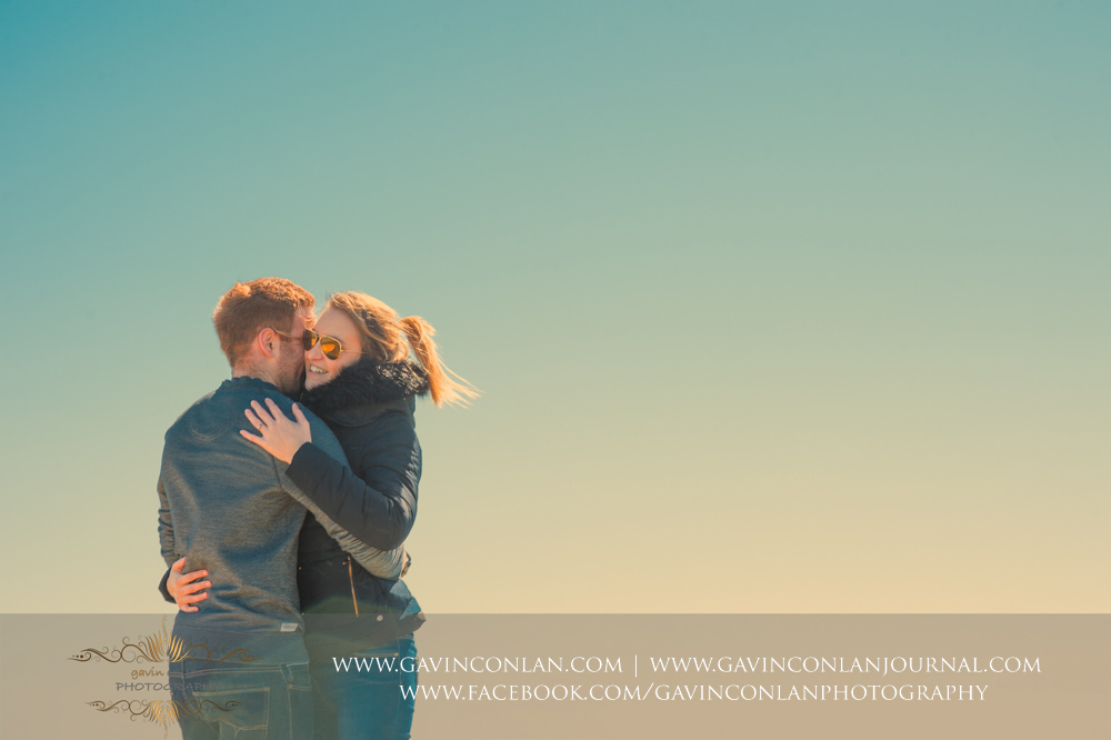 creative portrait of the couple cuddling bathed ingolden light at  Old Harry Rocks .Victoria and James Engagement Session in Bournemouth, Dorset by gavin conlan photography Ltd