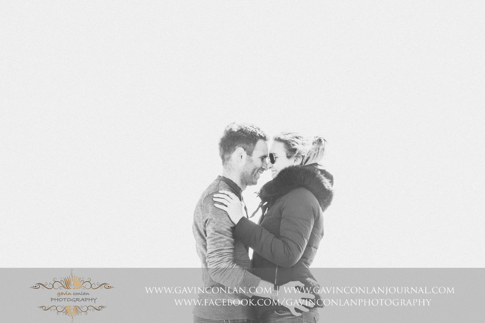 creative black and white portrait of the couple facing each other smiling at  Old Harry Rocks .Victoria and James Engagement Session in Bournemouth, Dorset by gavin conlan photography Ltd