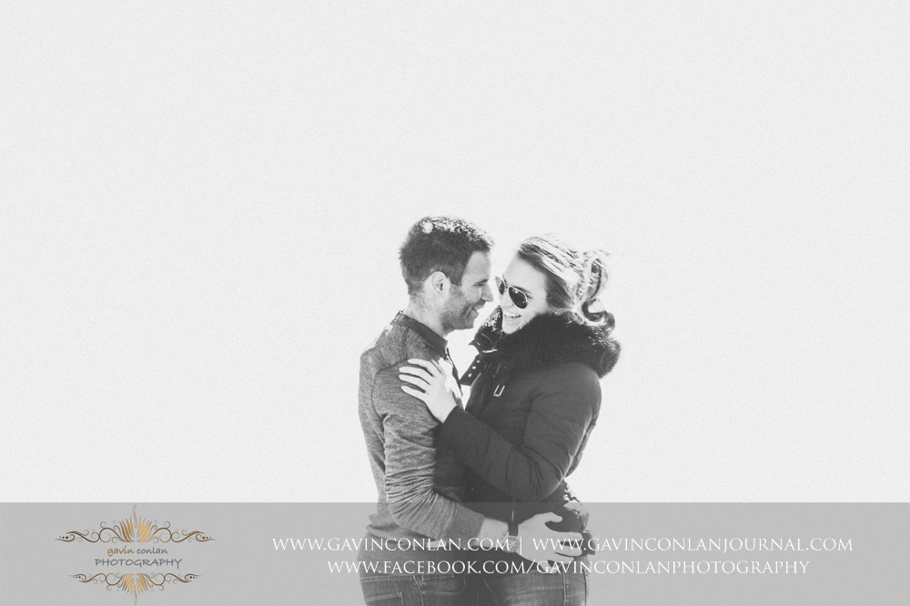 creative black and white portrait of the couple facing each other whilst laughing at  Old Harry Rocks .Victoria and James Engagement Session in Bournemouth, Dorset by gavin conlan photography Ltd