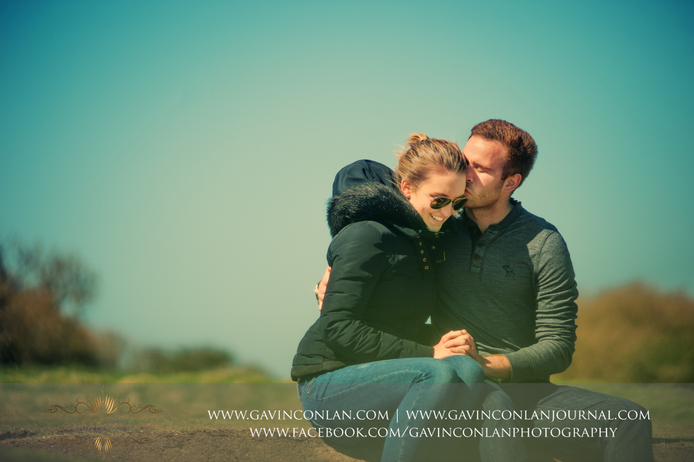 creative portrait of Victoria and James sitting down kissing at  Old Harry Rocks . Engagement Session in Bournemouth, Dorset by  gavin conlan photography Ltd