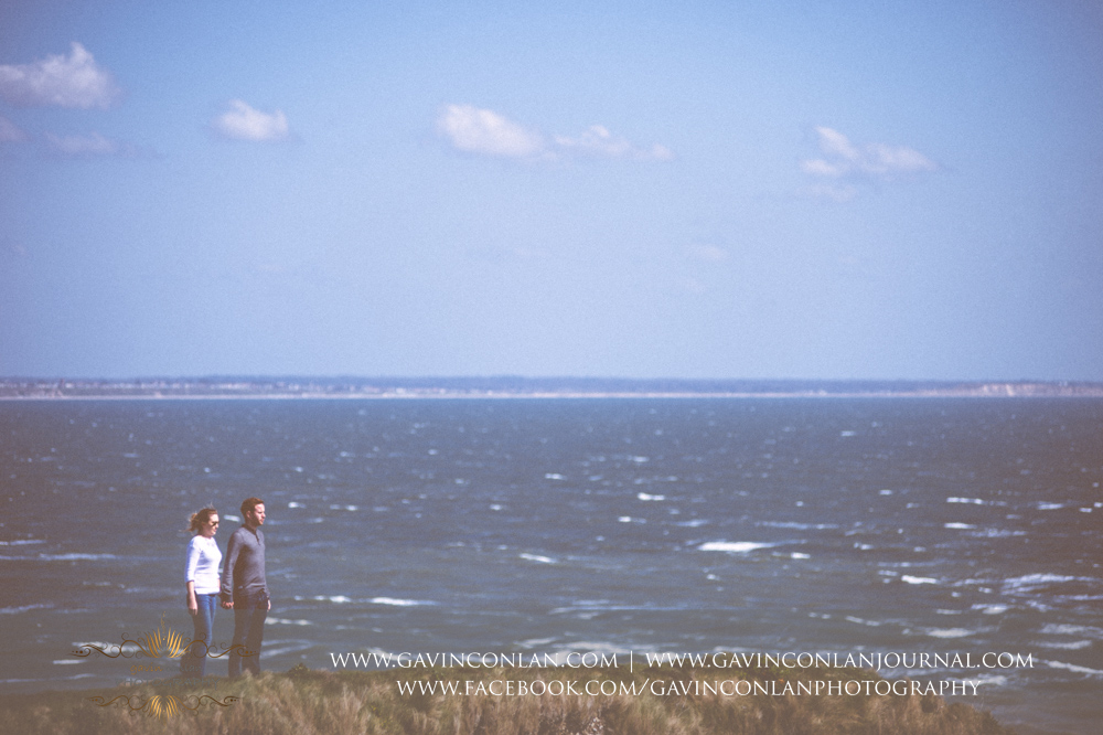 creative fine art portrait of Victoria and James standing on the edge of the chalk ridge holding hands looking out over the Solent at  Old Harry Rocks .Engagement Session in Bournemouth, Dorset by gavin conlan photography Ltd