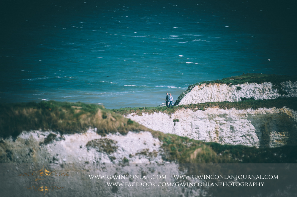 Victoria and James holding hands walking along the chalk ridge at  Old Harry Rocks .Engagement Session in Bournemouth, Dorset by gavin conlan photography Ltd