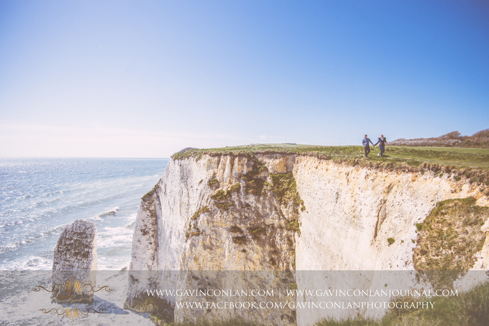 Victoria and James walking along the cliffs edge holding hands at  Old Harry Rocks . Engagement Session in Bournemouth, Dorset by  gavin conlan photography Ltd