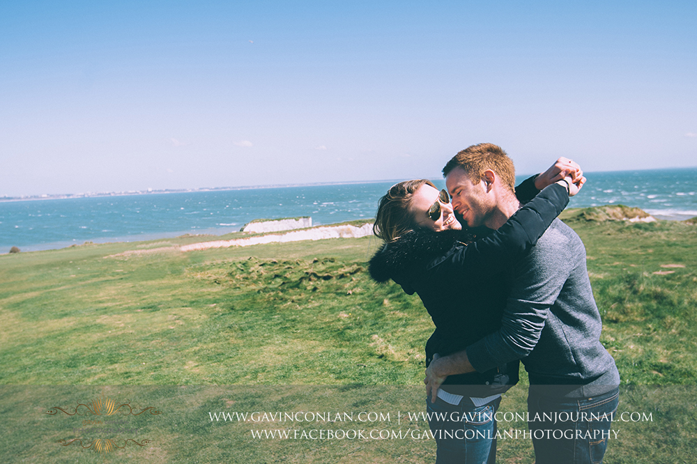 Victoria and James cuddling and smiling at  Old Harry Rocks .Engagement Session in Bournemouth, Dorset by gavin conlan photography Ltd