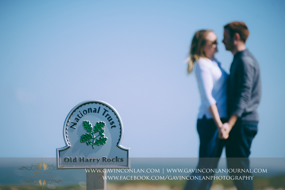 close up of the National Trust  Old Harry Rocks  sign withVictoria and James in the background. Engagement Session in Bournemouth, Dorset by gavin conlan photography Ltd