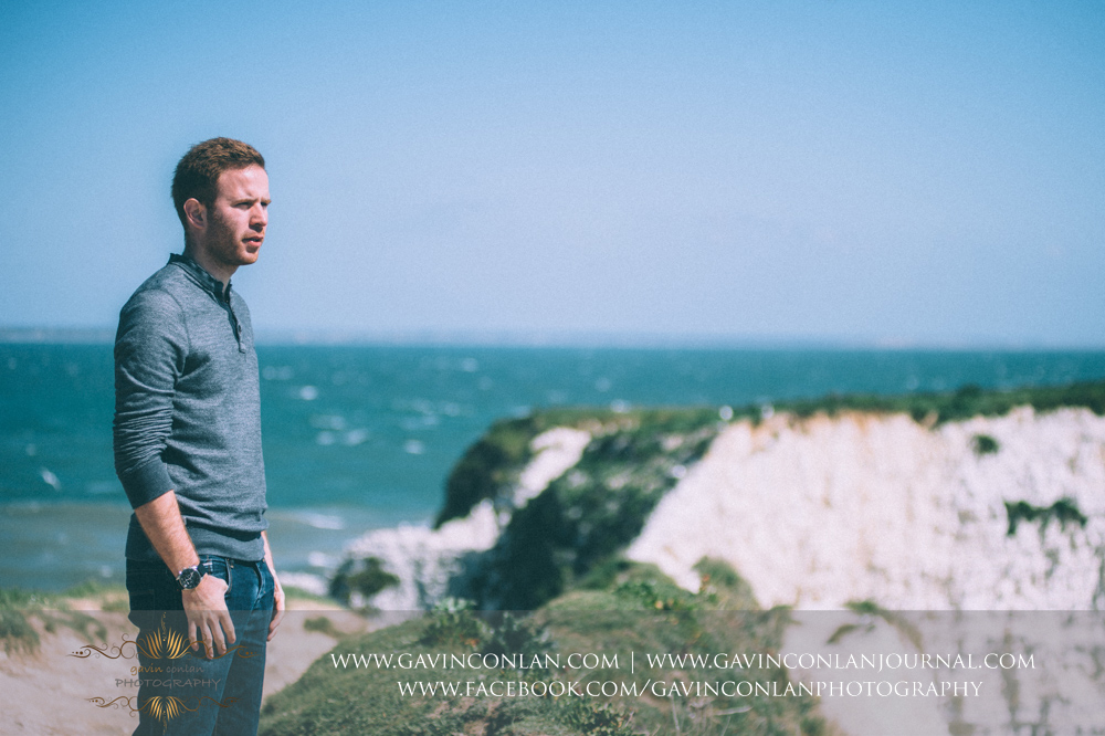 portrait of James looking out to the Solent at  Old Harry Rocks .Victoria and James Engagement Session in Bournemouth, Dorset by gavin conlan photography Ltd