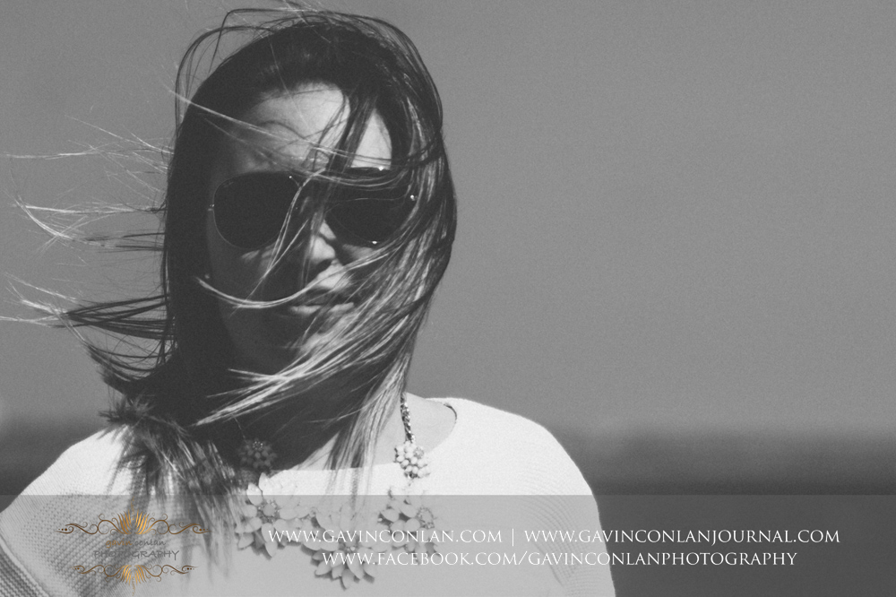 creative black and portrait of Victoria showing the wind blowing through her hair at  Old Harry Rocks .Victoria and James Engagement Session in Bournemouth, Dorset by gavin conlan photography Ltd
