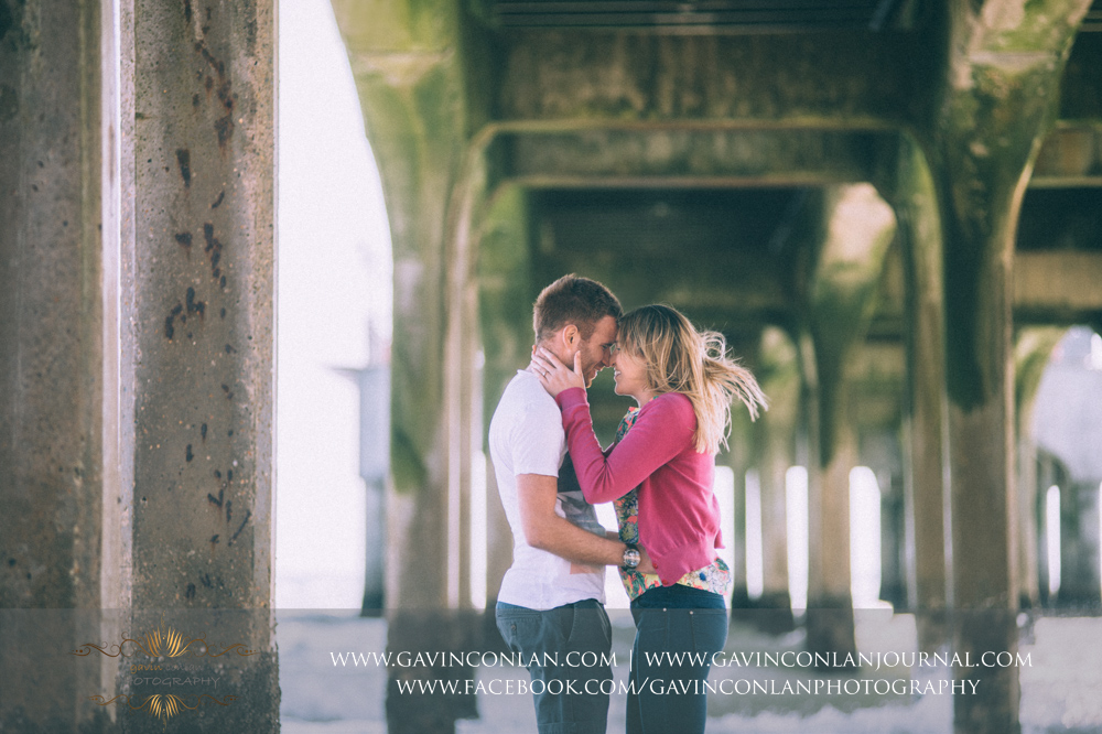 creative portrait of Victoria holding James' face just before she leans in to kiss him underneath  Boscombe Pier . Engagement Session in Bournemouth, Dorset by  gavin conlan photography Ltd