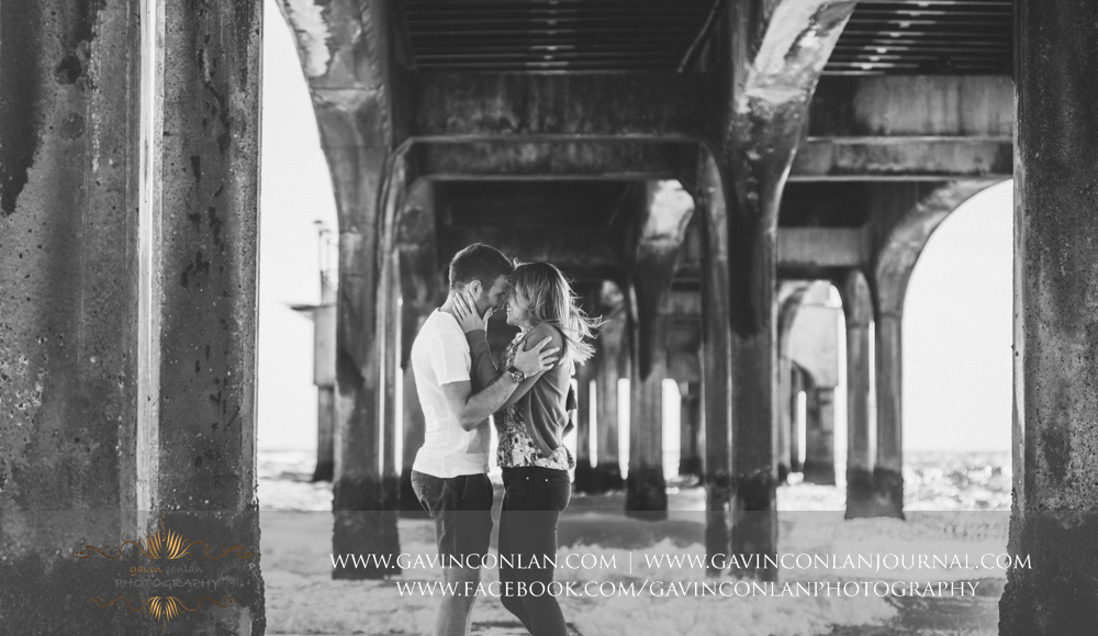 creative black and white portrait of Victoria and James which is full of emotion underneath  Boscombe Pier . Engagement Session in Bournemouth, Dorset by  gavin conlan photography Ltd