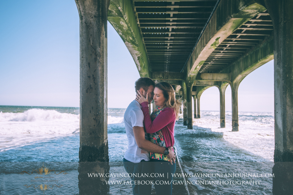 creative romantic portrait of Victoria and James underneath  Boscombe Pier . Engagement Session in Bournemouth, Dorset by  gavin conlan photography Ltd