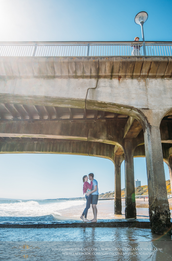 creative fine art portrait of Victoria and James about to kiss each other underneath  Boscombe Pier . Engagement Session in Bournemouth, Dorset by  gavin conlan photography Ltd