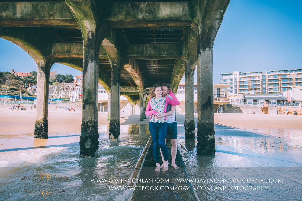 creative fashion portrait of Victoria and James posing underneath  Boscombe Pier  with the beach in the background. Engagement Session in Bournemouth, Dorset by  gavin conlan photography Ltd