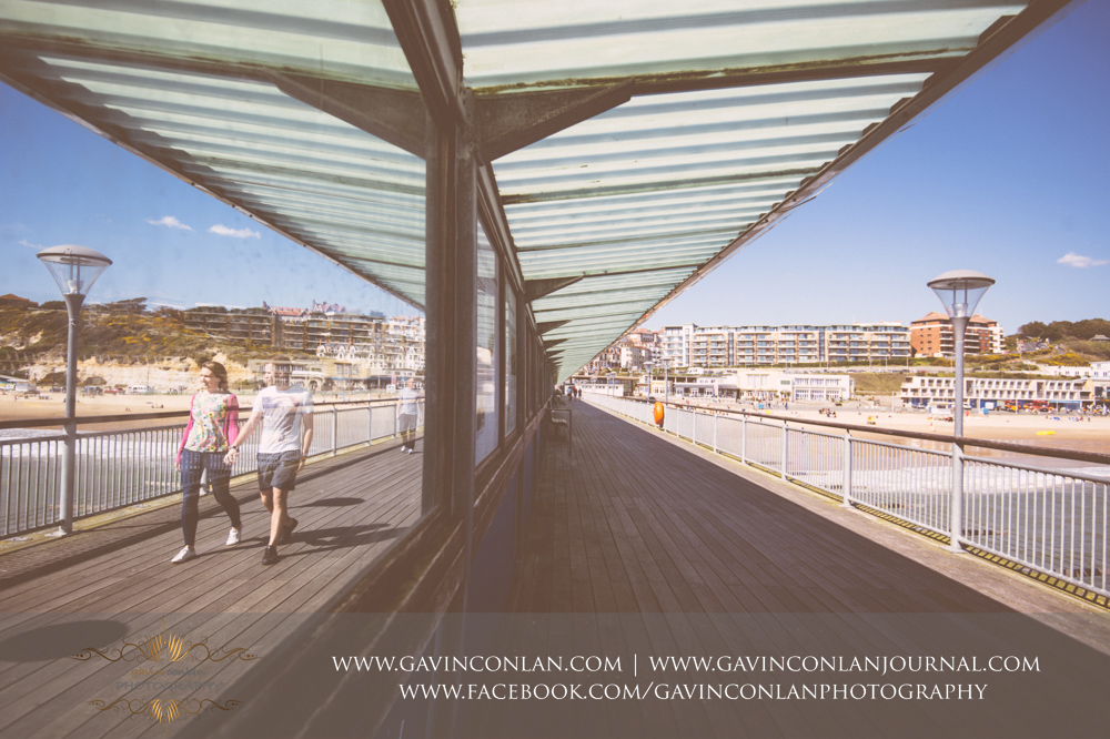 creative portrait of Victoria and James walking along Boscombe Pier with the beach in the background.Victoria and James Engagement Session in Bournemouth, Dorset by gavin conlan photography Ltd