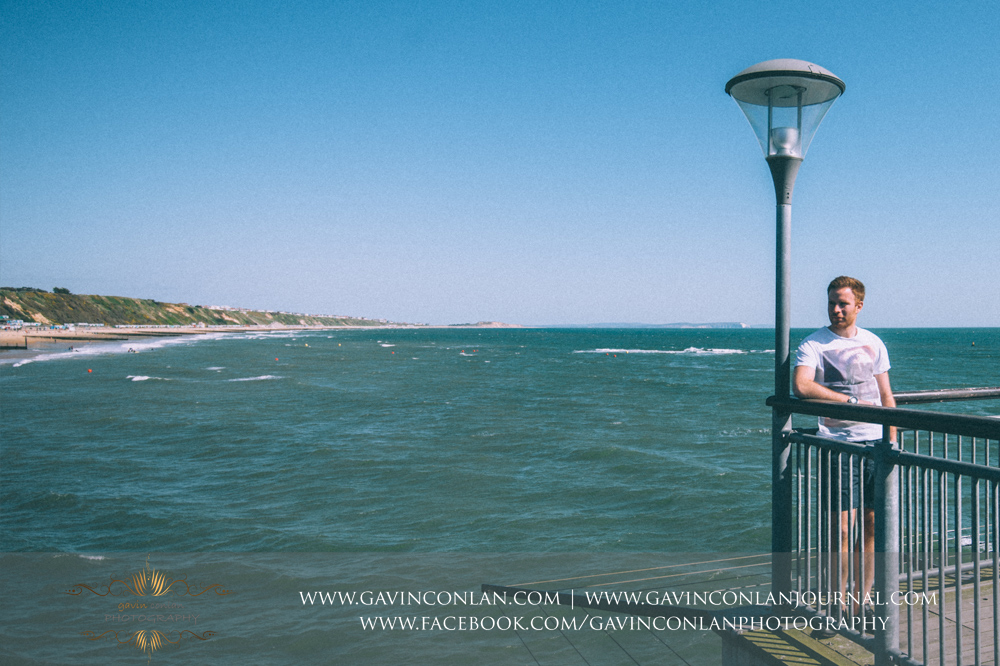 creative portrait of James on  Boscombe Pier . Victoria and James Engagement Session in Bournemouth, Dorset by  gavin conlan photography Ltd