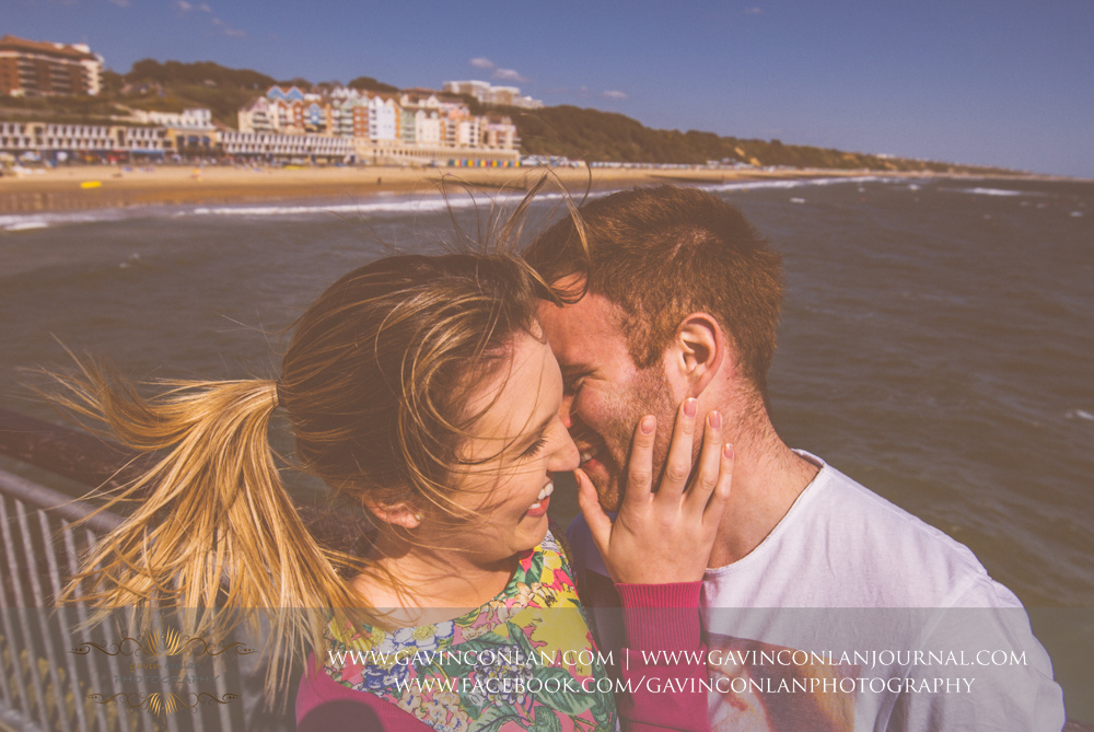 amazing portrait of Victoria and James sharing a priceless moment together on  Boscombe Pier . Engagement Session in Bournemouth, Dorset by  gavin conlan photography Ltd
