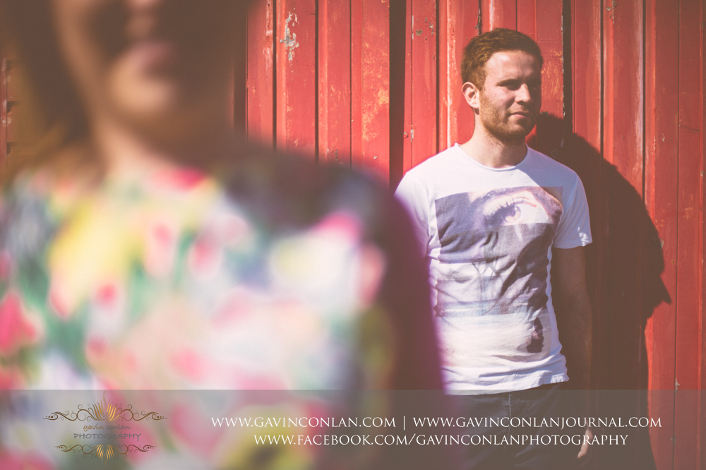 creative portrait of James in front of a red beach hut at  Boscombe Pier .Victoria and James Engagement Session in Bournemouth, Dorset by gavin conlan photography Ltd