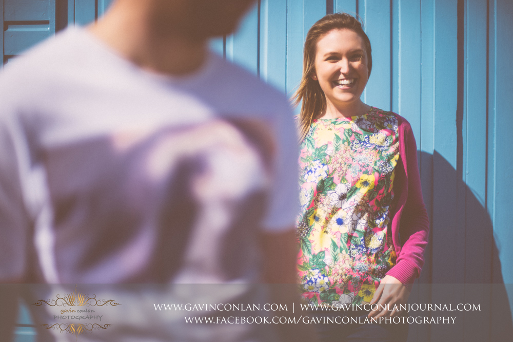creative fine art portrait of Victoria in front of a blue beach hut at Boscombe Pier .Victoria and James Engagement Session in Bournemouth, Dorset by gavin conlan photography Ltd