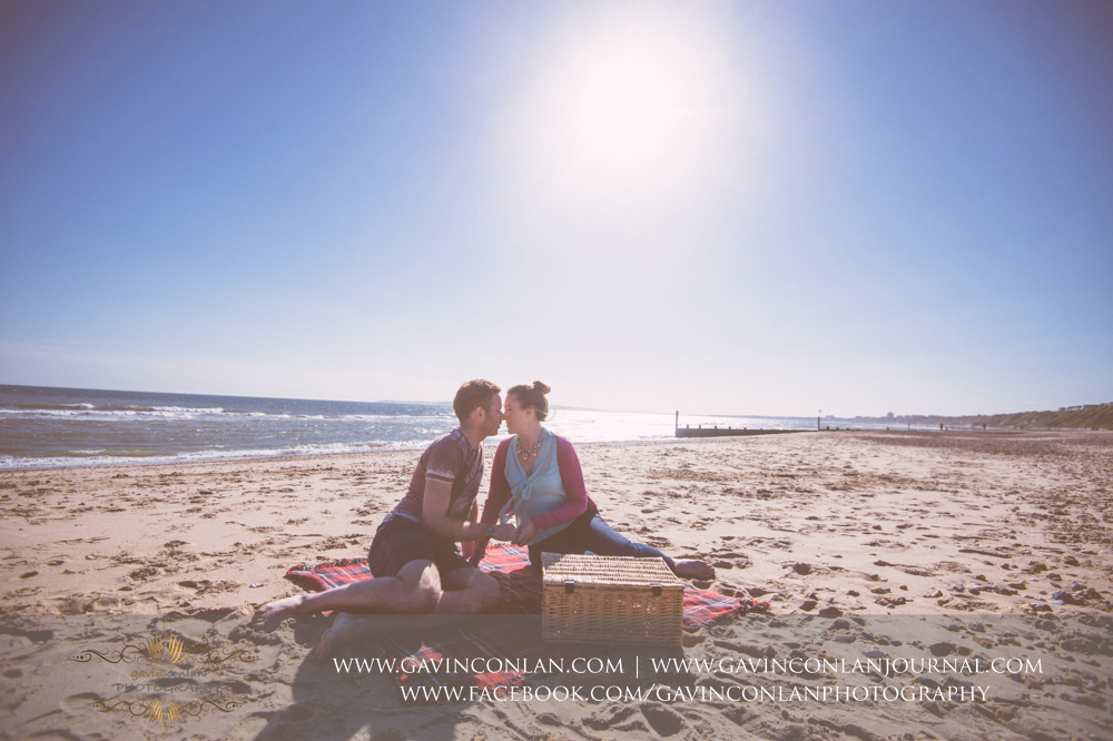 creative portrait of Victoria and James about to share a kiss on the beach near  Boscombe Pier . Engagement Session in Bournemouth, Dorset by  gavin conlan photography Ltd