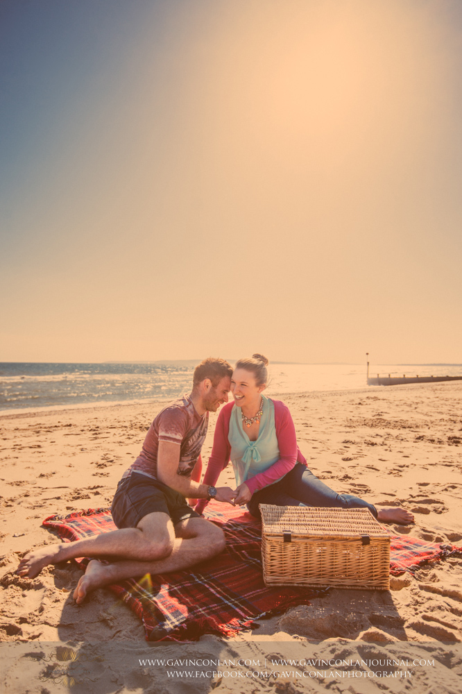 creative portrait of Victoria and James laughing on the beach near Boscombe Pier .Engagement Session in Bournemouth, Dorset by gavin conlan photography Ltd