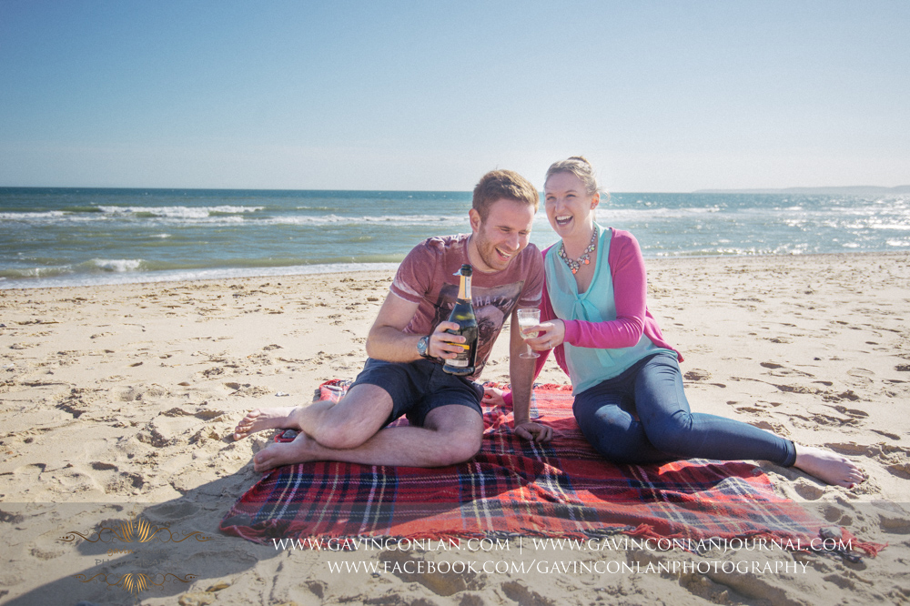 portrait of Victoria and James sitting on the beach near  Boscombe Pier  laughing will pouring their champagne. Engagement Session in Bournemouth, Dorset by  gavin conlan photography Ltd
