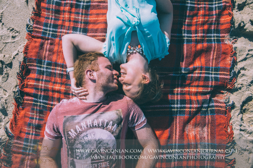 creative portrait of Victoria and James laying down on their blanket whilst looking at each other on the beach near  Boscombe Pier .Engagement Session in Bournemouth, Dorset by gavin conlan photography Ltd
