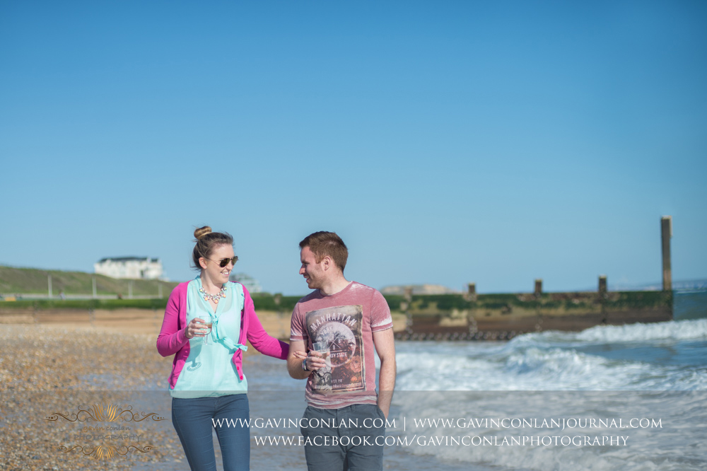 creative and fun portrait of Victoria and James walking along the beach near  Boscombe Pier . Engagement Session in Bournemouth, Dorset by  gavin conlan photography Ltd