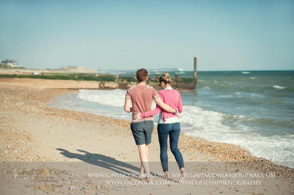 creative portrait of Victoria and James walking along the beach near  Boscombe Pier  arm in arm. Engagement Session in Bournemouth, Dorset by  gavin conlan photography Ltd