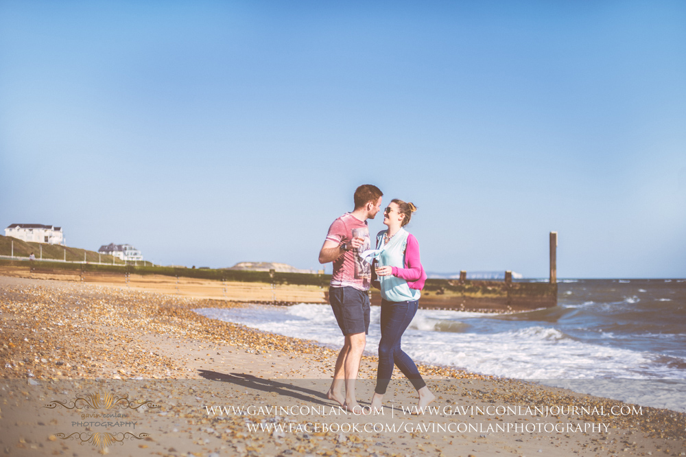 creative fun portrait of Victoria and James on the beach near  Boscombe Pier . Engagement Session in Bournemouth, Dorset by  gavin conlan photography Ltd