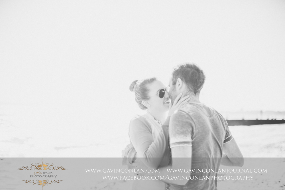 creative black and white portrait of Victoria and James sharing a kiss on the beach near  Boscombe Pier .Engagement Session in Bournemouth, Dorset by gavin conlan photography Ltd