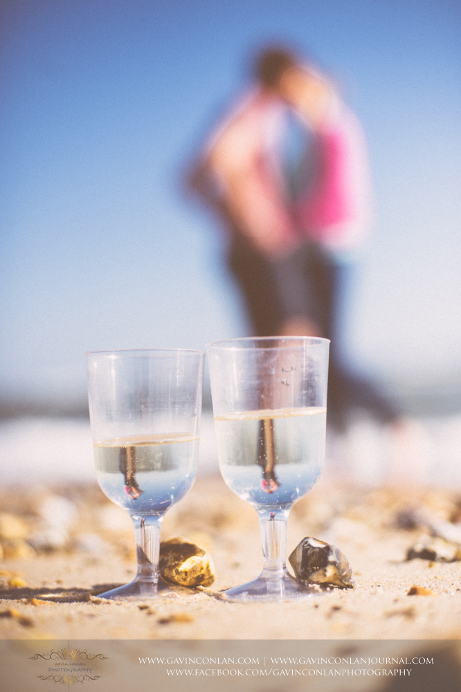 creative portrait showcasing two glasses of champagne on the beach near  Boscombe Pier .Victoria and James Engagement Session in Bournemouth, Dorset by gavin conlan photography Ltd